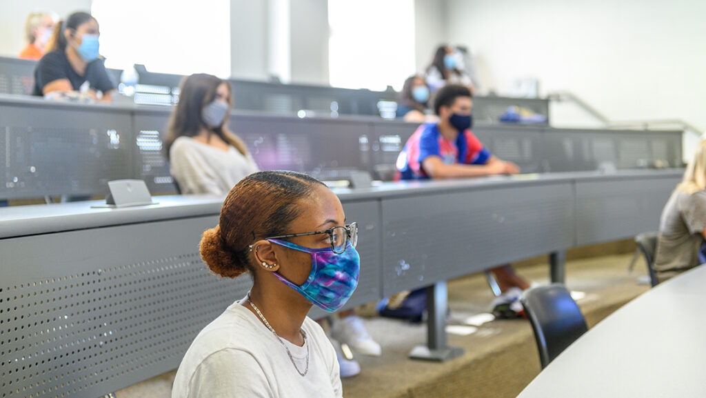 Students wearing masks sitting 6 feet apart in a classroom