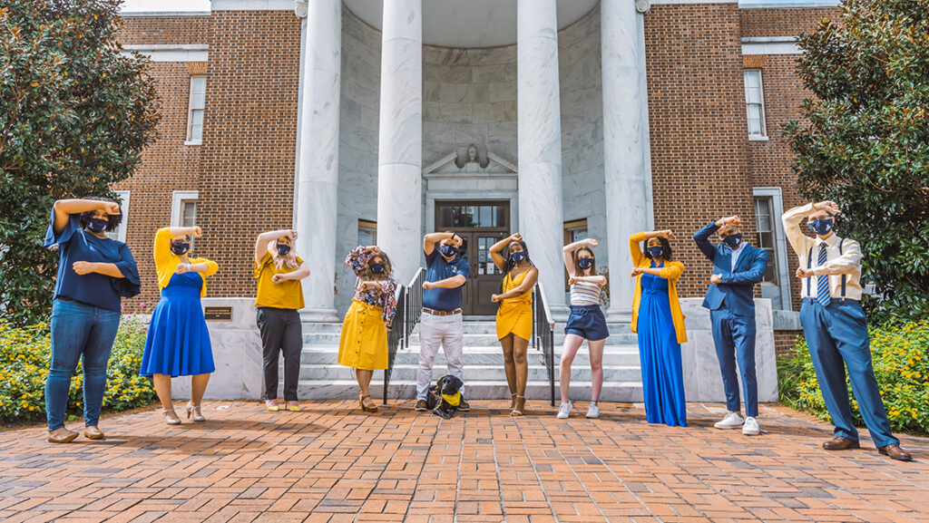 """Homecoming court students pose in face coverings, making the """"G"""" sign with their arms"""