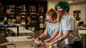 Two students wearing masks chopping fresh vegetables at Spartan Open Pantry