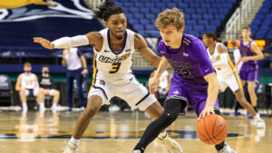 Action shot from basketball game in which UNCG player defends opponent