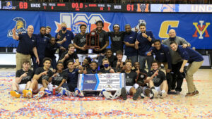 Men's basketball team holding the NCAA Tournament Ticket Punched sign after winning championship game