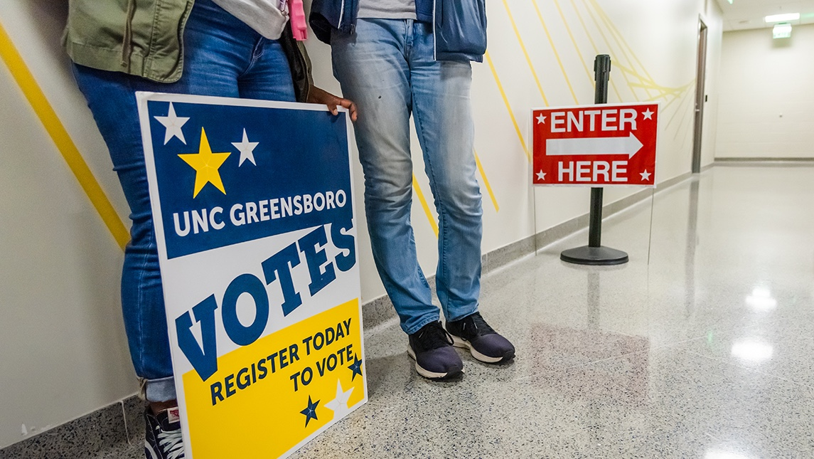 """Students stand with sign that reads """"UNC Greensboro VOTES; Register today to vote"""""""