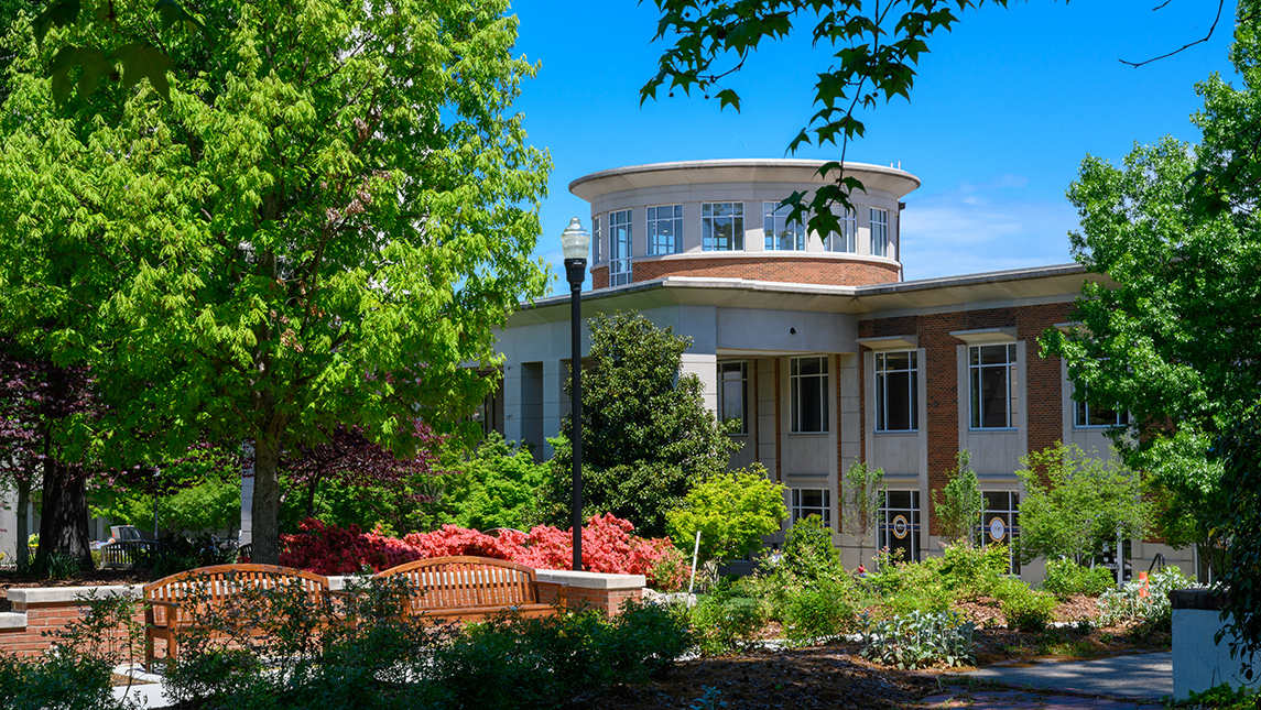 Photo of campus building with spring foliage