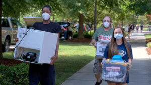 Three people wearing masks and carrying belongings into the dorm during move-in