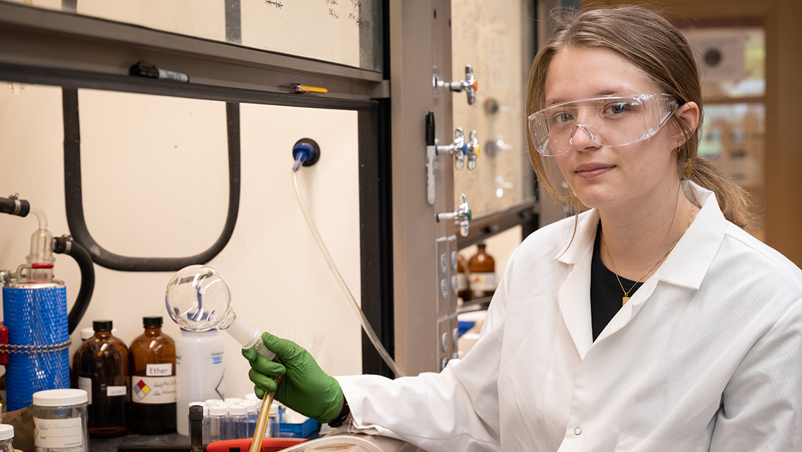Student in white lab coat holding instrument in science lab