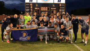 Photo of men's soccer team holding up trophy and banners after title win