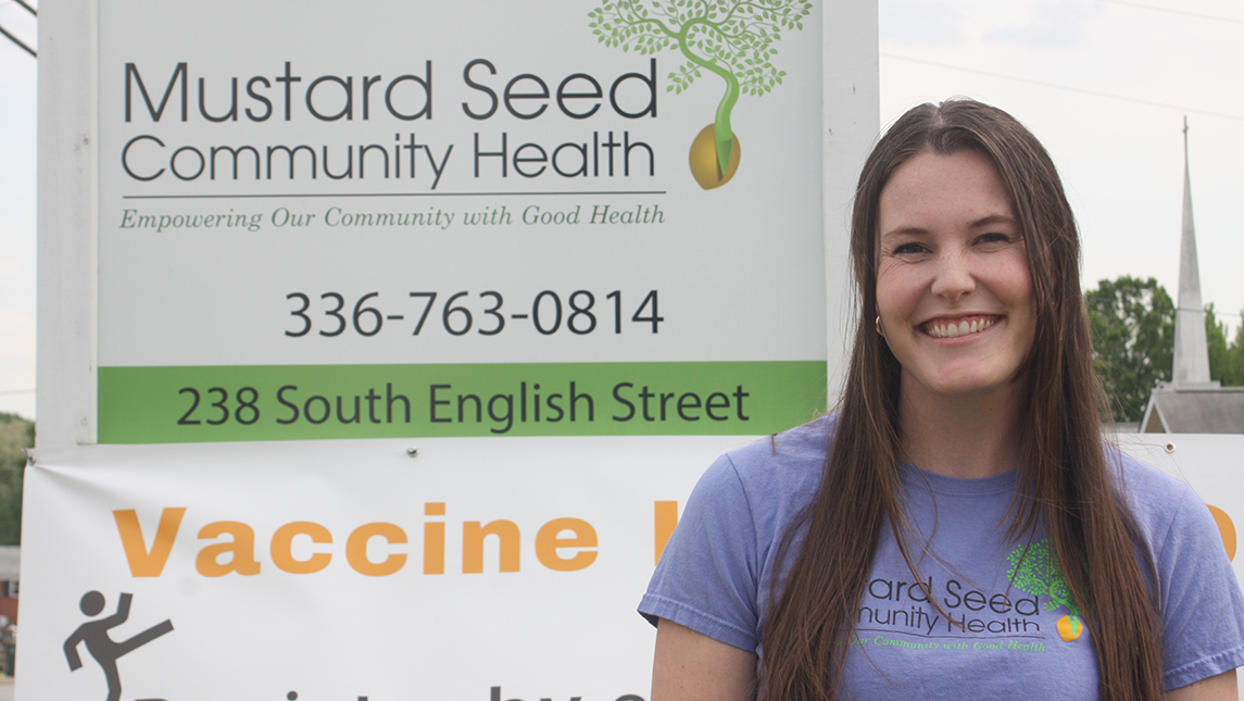 """Caroline Wells smiling in front of """"Mustard Seed Community Health"""" sign"""