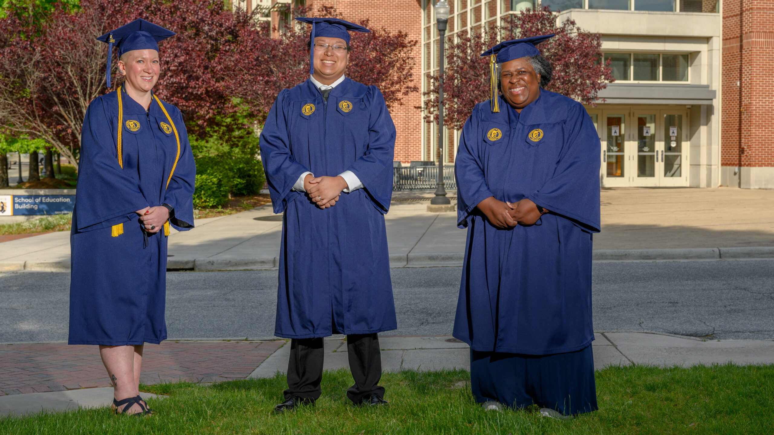 Jessica Jeffus, Jimmy Vang, and Lynnette Pitts pose in their cap and gown in front of the School of Education Building