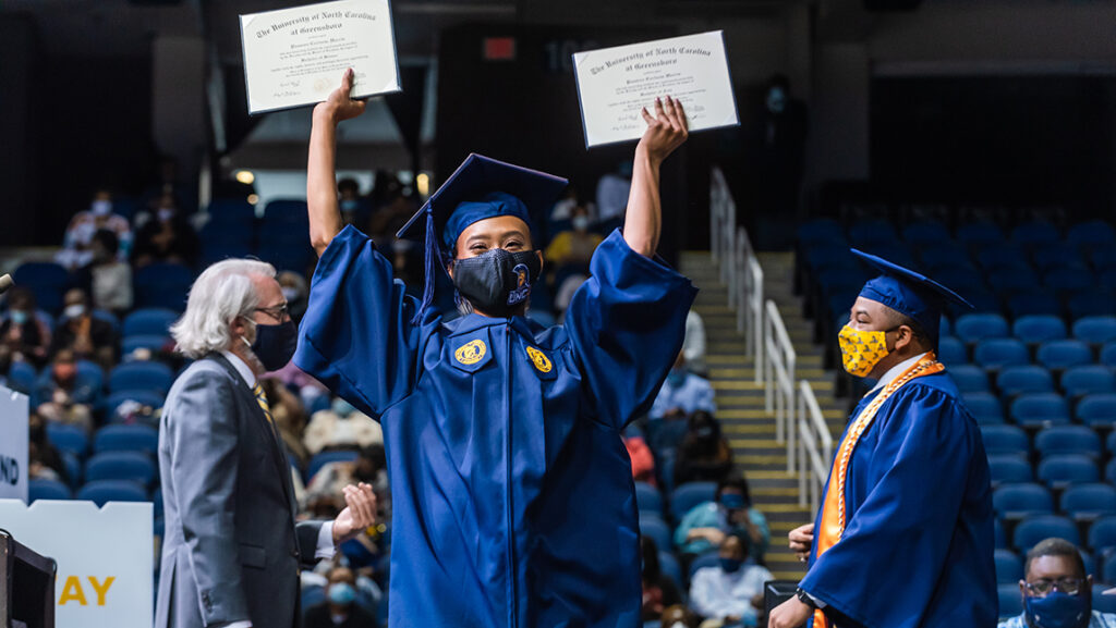 Student holding up two diplomas on stage at commencement