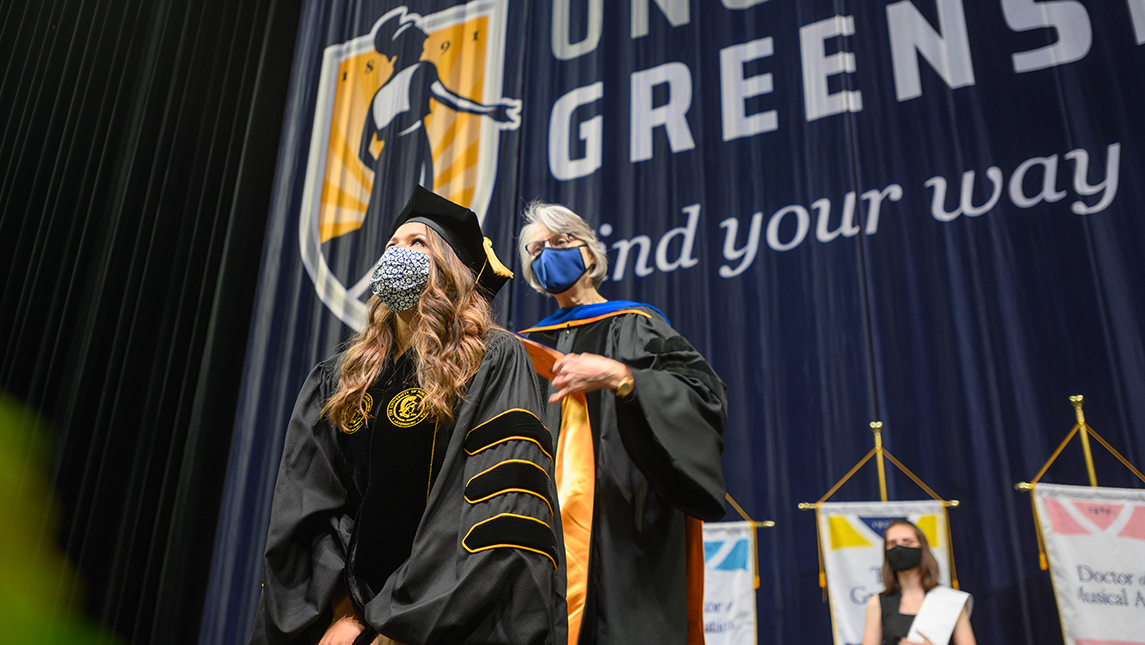 Doctoral student getting hooded at commencement