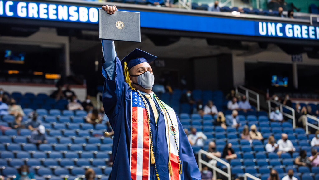 Student holding up diploma in celebration at commencement