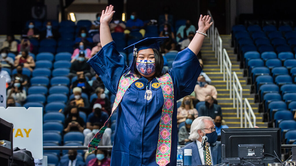 Student holding up hands in celebration at commencement