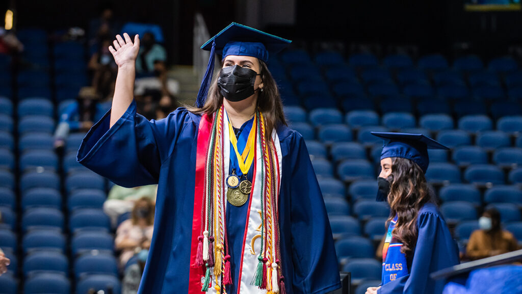 Student waving while crossing the stage on commencement