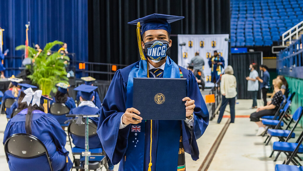 Student holding up diploma cover with UNCG branded mask at commencement
