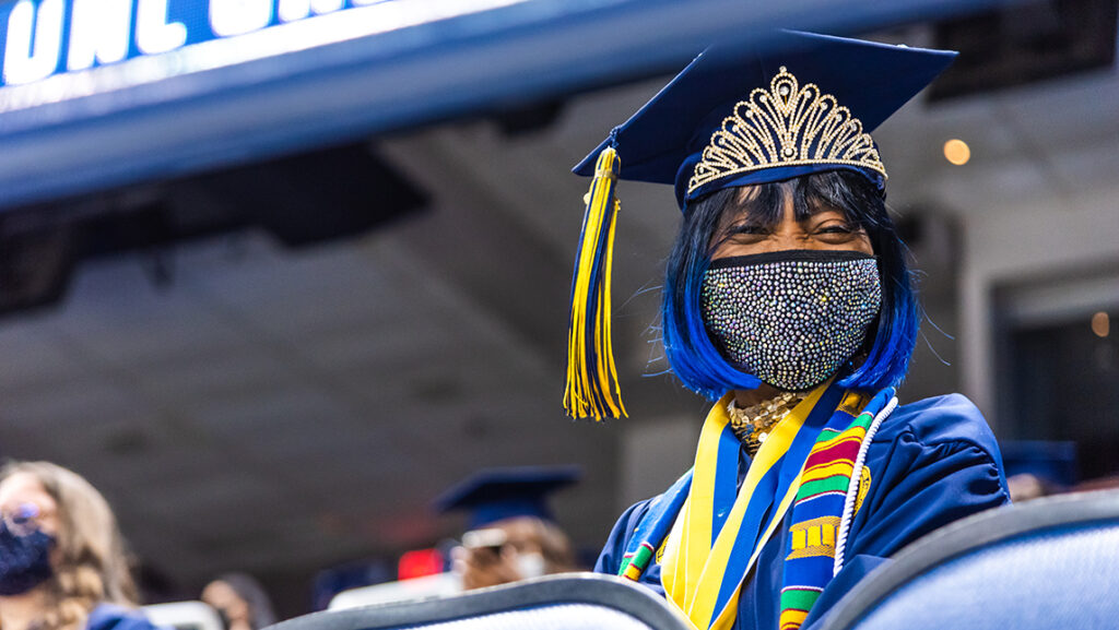 Student smiling (under mask) at commencement