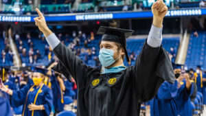 Student holding up both hands in celebration at commencement
