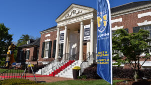 Exterior of Alumni House with red carpet and alumni signage