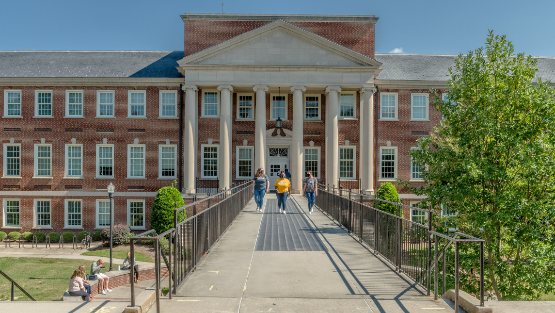 Student walking in front of Petty Building