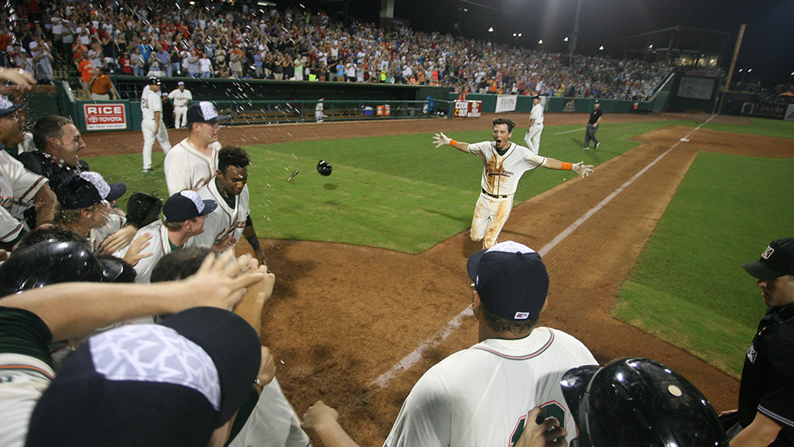 Baseball player running to home plate with teammates ready to celebrate with him at home plate