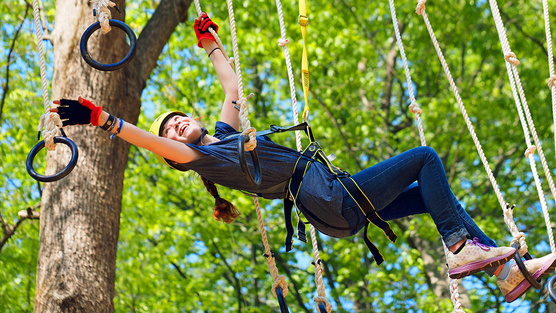 Girl playing in treetop adventure park