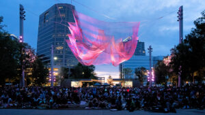 People in park downtown with art installation and downtown buildings lit up