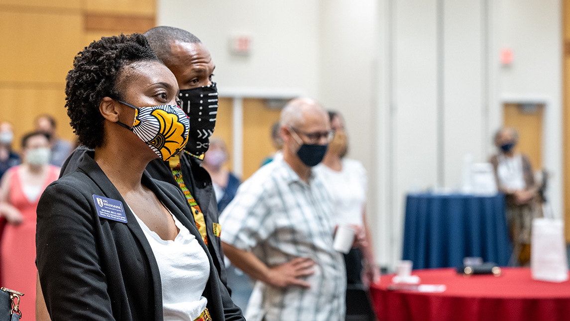 Masked event attendees listen to remarks