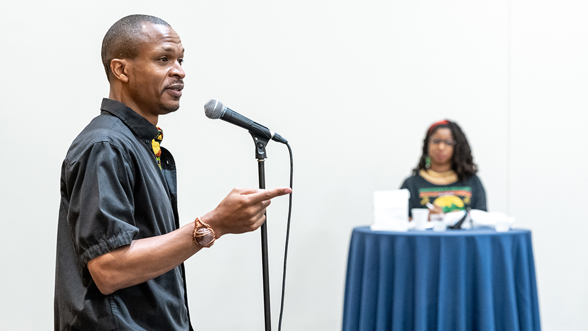Man speaks at microphone while woman looks on in the background