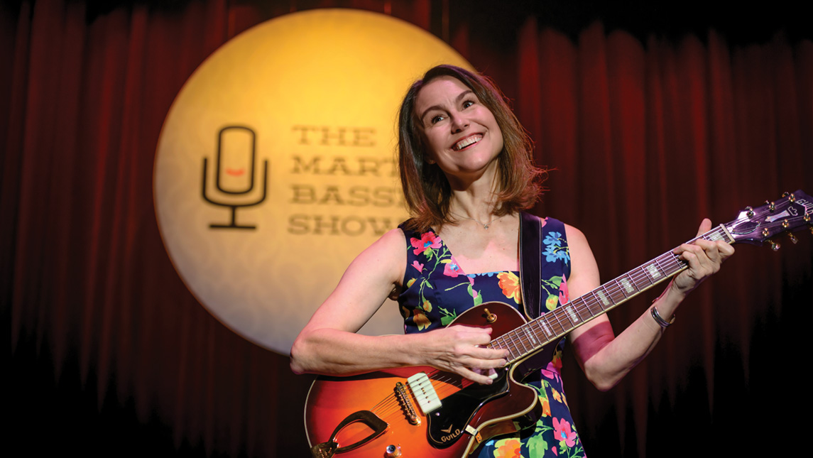 """Image of woman smiling and holding guitar on stage. Sign in the background says """"The Martha Bassett Show."""""""