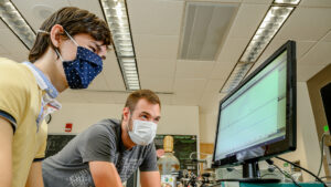 Image of two people in masks looking at computer screen in lab setting