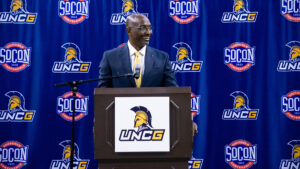 Photo of Mikes Jones smiling at podium during press conference