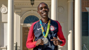 Man with Olympic gear and Silver medal in front of campus building