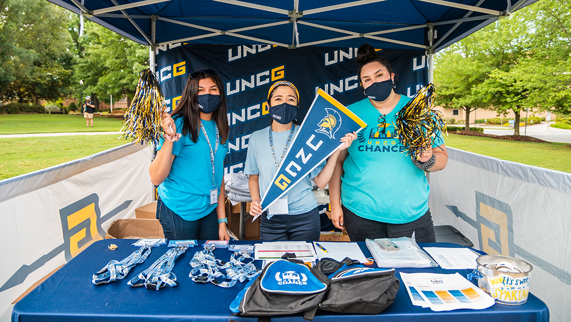 Three students pose in masks  with UNCG pom-poms and banner under a blue tent with CHANCE swag
