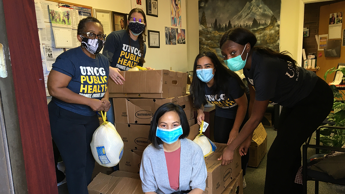 Dr. Morrison with four students wearing masks around a stack of boxes of supplies