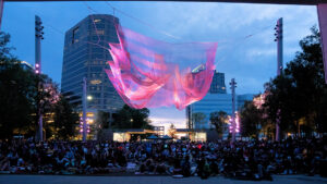 Crowd of people sitting underneath an art sculpture in Downtown Greensboro at night