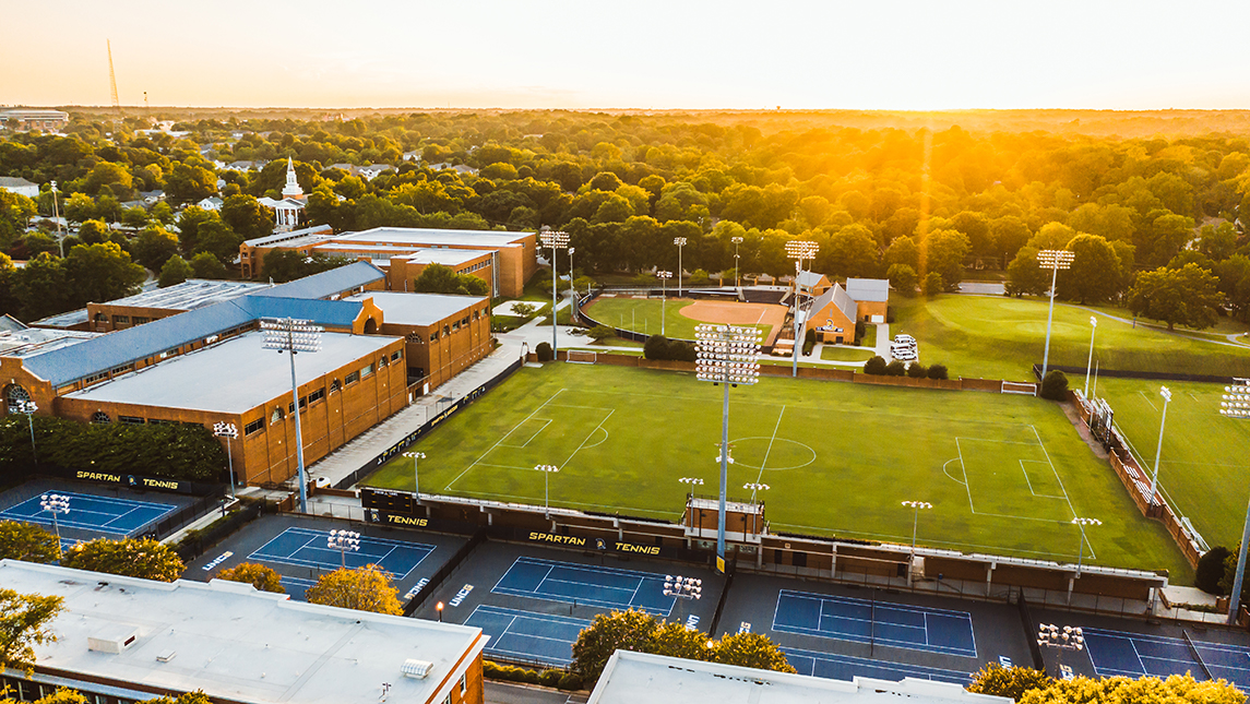 Aerial shot of UNCG's Coleman Building, soccer stadium, and tennis courts.