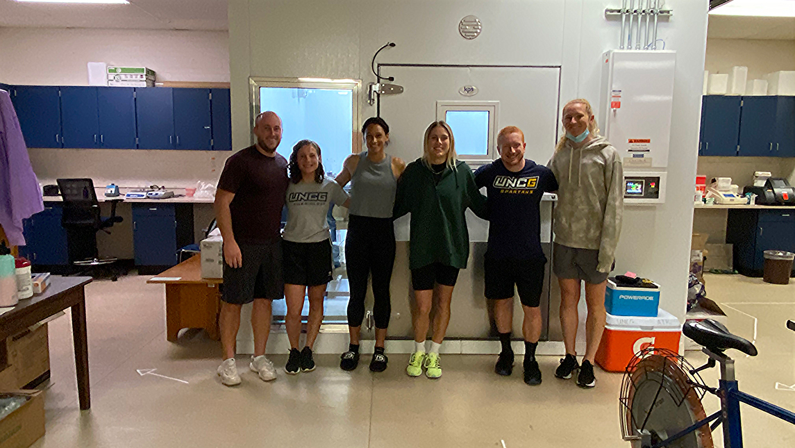 (L to R) Dr. William Adams, Emily Bechke (PhD student), Lynn Williams, Abby Dahlkemper, Mitchell Zaplatosch (PhD student), and Sam Mewis pose in the exercise physiology lab