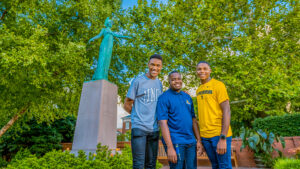 Christoff Hairston, Julian Kennedy, and Tavis Cunningham in front of Minerva Statue
