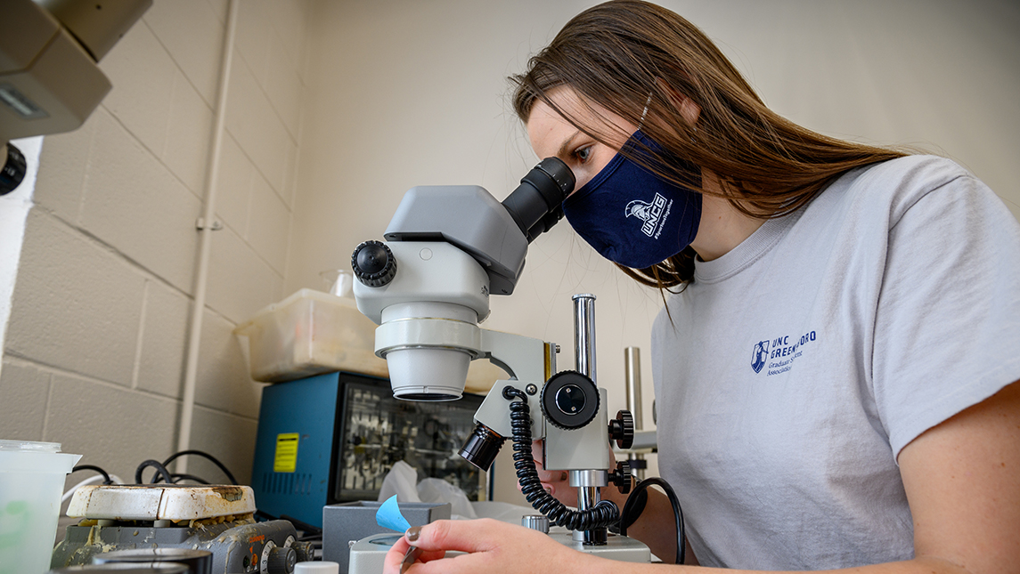 a student looking into a microscope while wearing a UNCG face covering and t-shirt