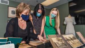 Kathelen SMith, Dr. Lisa Levenstein, and Dr. Mandy Cooper look at artifacts and archived material on suffrage