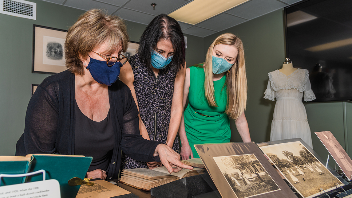 Smith, Levenstein, and Cooper look at artifacts about the women's suffrage movement on State Normal's campus