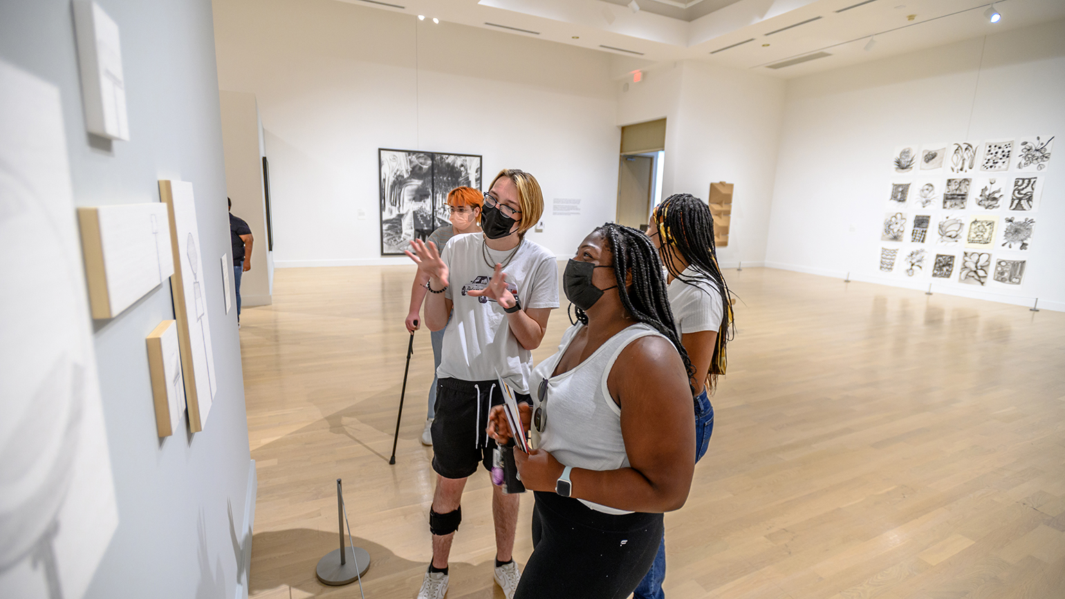 """Students view the Weatherspoon Art Museum's """"Art on Paper"""" exhibit."""