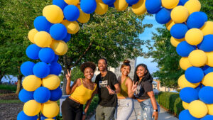 four students pose under a blue and gold balloon arch